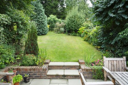 Terraced and landscaped back garden in England UK with patio, grass and stone steps Reklamní fotografie