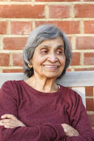 Old elderly Asian Indian woman sitting with a smiling face, depicting health and happiness in old age and retirement