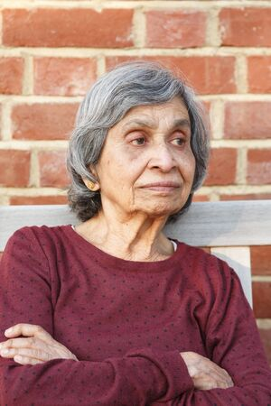 Elderly Asian Indian woman sitting alone. Healthy and slim appearance, may also depict loneliness or depression in old age.