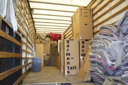 Kisten verpacken und in die Ladefläche eines großen Umzugswagens oder Lieferwagens packen