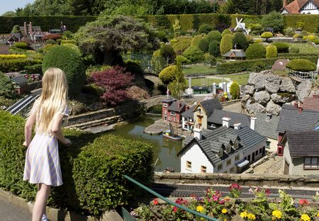 Beaconsfield, UK - June 27, 2019. A young girl visitor looks at miniature houses in Bekonscot Model Village and Railway, a popular visitor attraction in Buckinghamshire, England