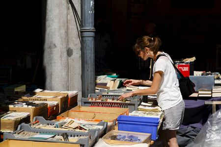 Lille, France - July 20, 2013. A woman browses at a book stall in La Vieille Bourse de Lille, the historic former stock exchange in the centre of Lille, France
