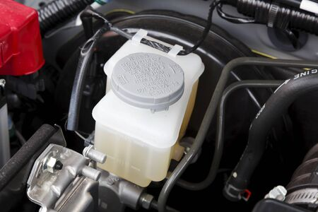 Buckingham, UK - May 16, 2019. Brake fluid container and filler cap in a car engine compartment. The brake fluid levels can be seen on the side.