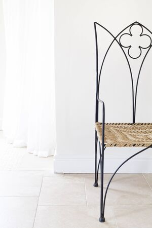 Wrought iron modern chair against a wall in a home interior Фото со стока