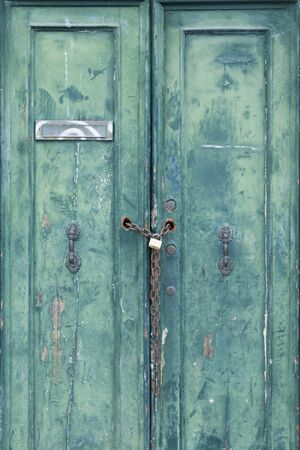 Old locked door with peeling paint, padlock and chain in Venice, Italy Banco de Imagens