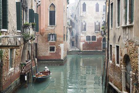 Venedig-Kanalszene, die ein kleines Boot in einem ruhigen Wohnviertel von Venedig im Winter an einem kühlen nebligen Tag ohne Leute oder Touristen darstellt