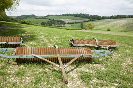Farming in the UK with farm equipment (Cambridge roller or cultipacker) in a field in Oxfordshire countryside