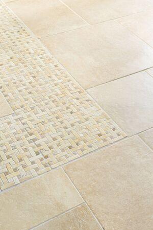 Porcelain floor tiles with a stone mosaic design in a neutral cream colour