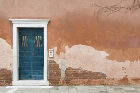 Vintage front door painted blue and a wall with old weathered render in Venice, Italy Stock Photo