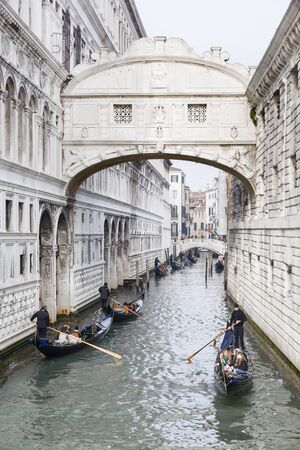 VENICE, ITALY - December 24, 2012. Gondoliers take tourists on a gondola ride under the Bridge of Sighs in Venice, Italy Editorial