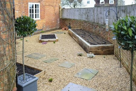 Small garden design with hard landscaping, gravel and york stone path, oak sleeper raised beds and bay trees