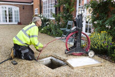 BUCKINGHAM, UK - October 16, 2019. A professional drain cleaning engineer inspects a blocked household drain