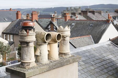 Chimney pots and roof tops in a typical Welsh town in the UK. With ornate Victorian cowls. Conwy, Wales