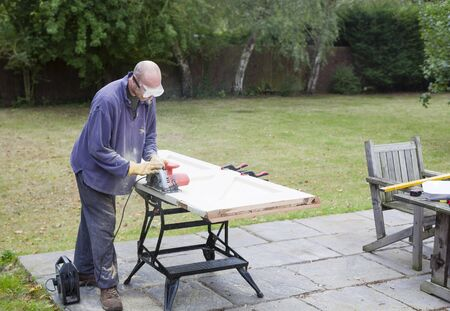 DIY carpentry and home improvement, man using a circular saw to resize a wooden door, UK