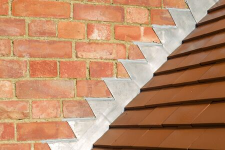 Closeup of new plain red clay tiles and lead flashing on a pitched roof in the UK
