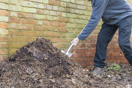 Composting, man turning a compost heap in a garden, UK