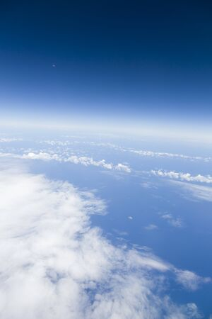 View from window of an airplane of the moon, blue sky, clouds and Atlantic ocean. Depicts Earth, environment, global concept