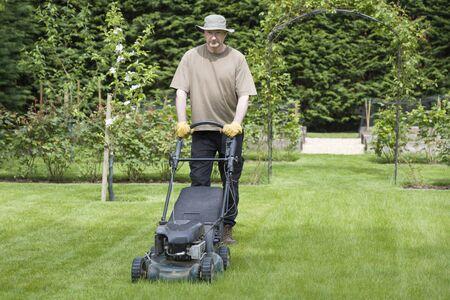Man mowing a lawn in the grounds of a luxury home, lawncare and grass maintenance, UK