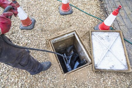 Man unblocking domestic sewage drain through open inspection chamber, drain cleaning company, UK