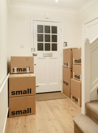 Packed and taped cardboard boxes stacked inside a room of a home, moving house, UK