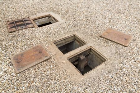 Inspecting an underground septic tank or rainwater system with open manhole cover, UK
