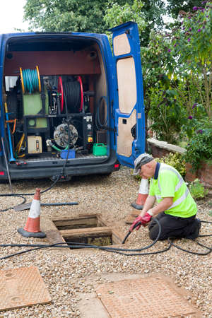 BUCKINGHAM, UK - August 07, 2015. Drain cleaning company, man jetting sewage drain outside house, UK