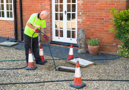 BUCKINGHAM, UK - August 07, 2015. Man jetting sewage drain outside house, drain cleaning company unblocking main sewage pipe, UK