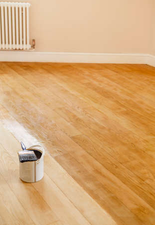 Sanding and staining a wooden floor in a room, UK Stock Photo