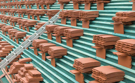New roof tiles stacked on a roof ready for laying on a house according to building regulations, UK