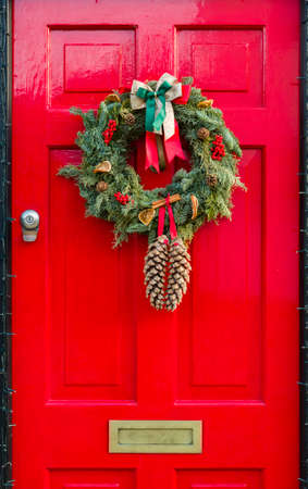 Detail of wooden front door to a UK house painted a festive bright red with Christmas wreath