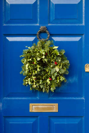Detail of blue front door with Christmas garland wreath made from holly Stock Photo