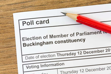 Poll card for a UK general election, voting information paper on desk with pencil