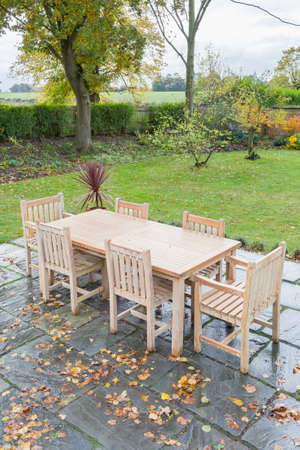 Large back garden in UK countryside in autumn, with wooden furniture on a garden patio terrace