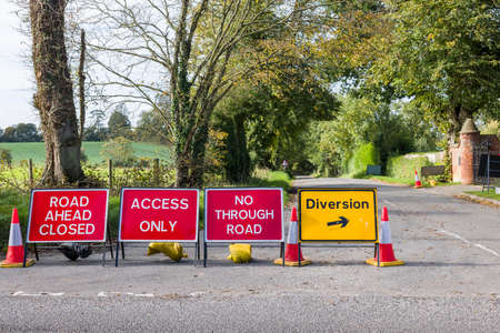 Road closed signs on a UK country road with yellow diversion sign