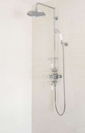 Shower with fixed rainfall shower head, slide rail and handset in a new, luxury bathroom, UK