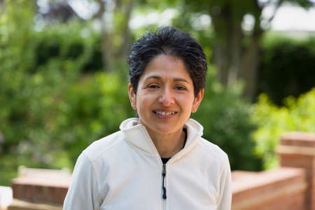 Casual portrait of an Indian woman smiling. British Asian (BAME) standing outdoors in a garden, UK