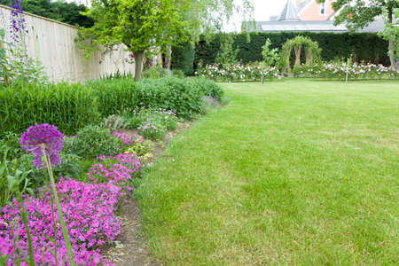 Large English garden in early summer or late spring with flowers in border and lawn. Example of landscaped garden design and gardening, UK