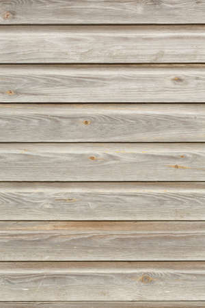 Clapboard or shiplap cladding, wood siding on an old building exterior, UK. Weathered oak timber texture