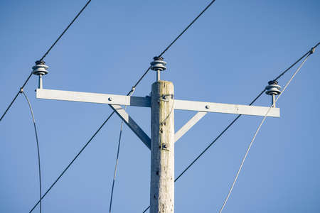 Electricity mains supply close up, overhead power lines against a blue sky, UK