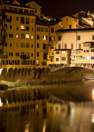 river arno: Reflections of the Ponte Vecchio in the River Arno by night