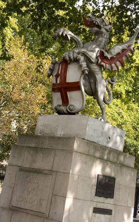 Statue of a dragon holding a shield with an English flag in London photo