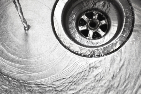 Stainless steel sink plug hole close up with water photo