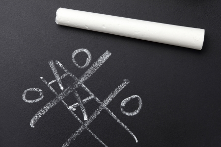 White chalk resting on black board with nought and crosses game photo