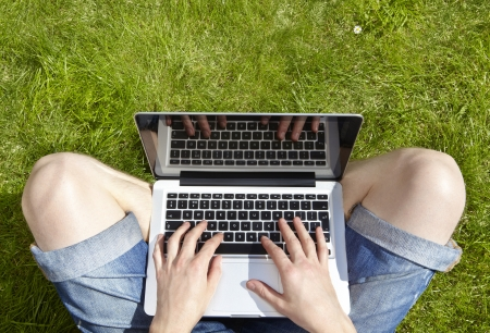Man using laptop on a summers day sitting outside on grass Stock Photo