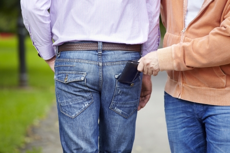 Man has his wallet pickpocketed whilst walking along the street photo