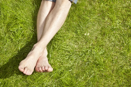 barefooted: Young Adult sunbathing on grass Stock Photo