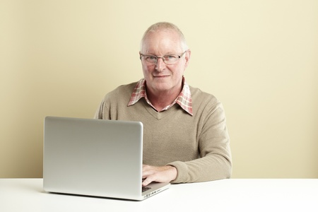 Senior man using laptop whilst smiling Stock Photo - 14615947