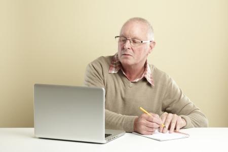 Senior man met behulp van laptop, terwijl het maken van notities