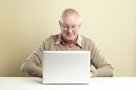Senior man met behulp van laptop, terwijl lachend Stockfoto
