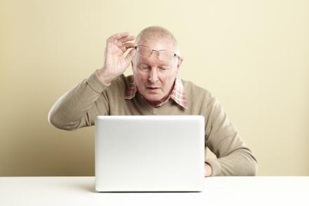 perplexing: Hombre mayor que usa la computadora port�til mientras que mirando confundido